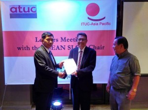ATUC Vice-President John De Payva, right, hands the ATUC Declaration to the SLOM Chair,  U Myo Aung, while TUCP Vice President Ruben Torres looks on.